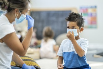 Teacher shows a student how to properly put on a mask