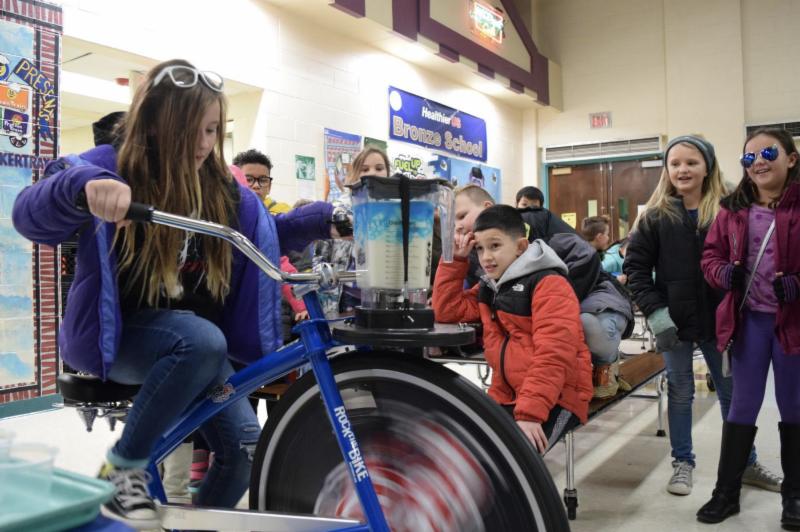 Knudsen Elementary School student Emma Simpson pedals a smoothie bike.