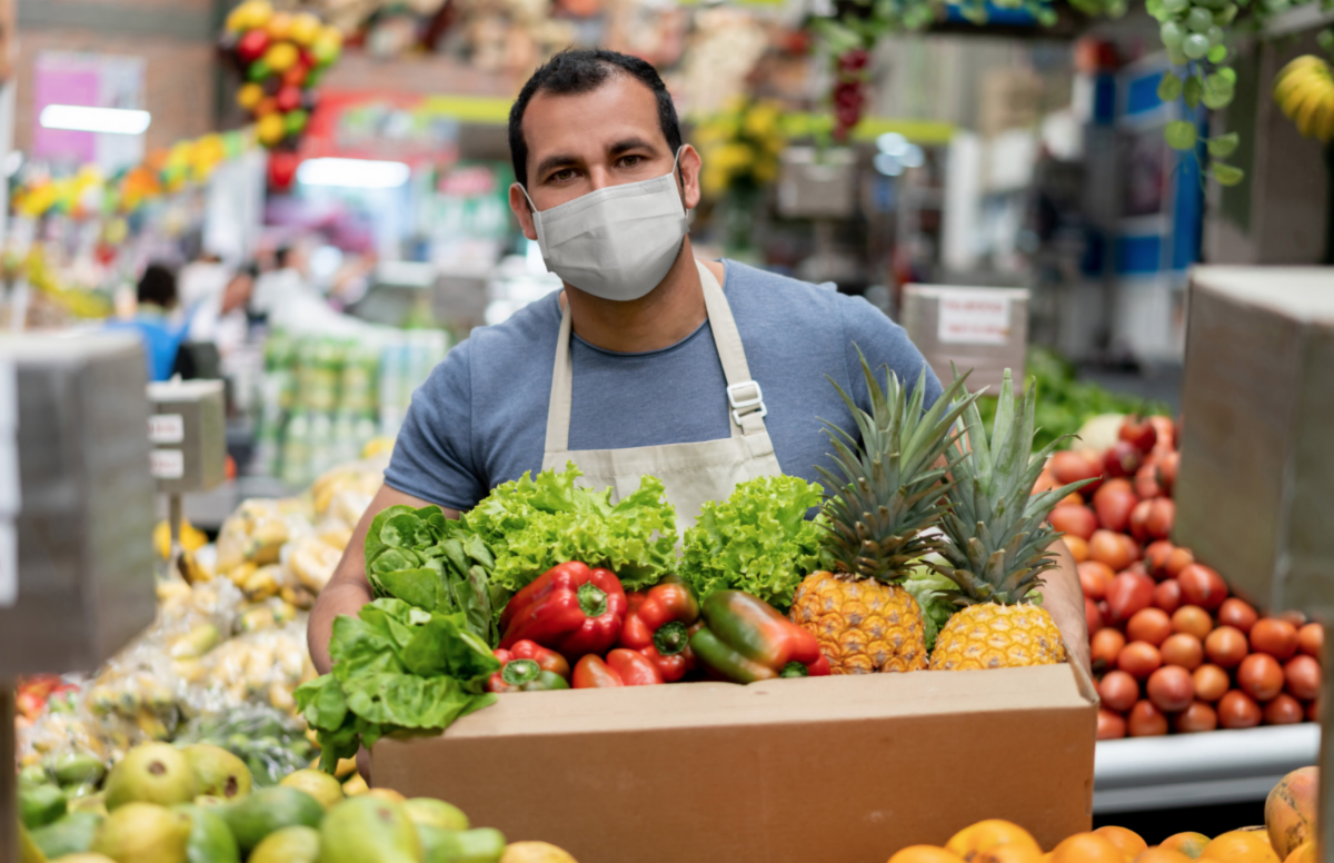 Man in a mask carries a box of fresh produce