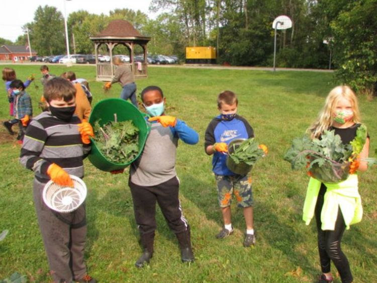 Students hold fresh produce harvested from the school garden