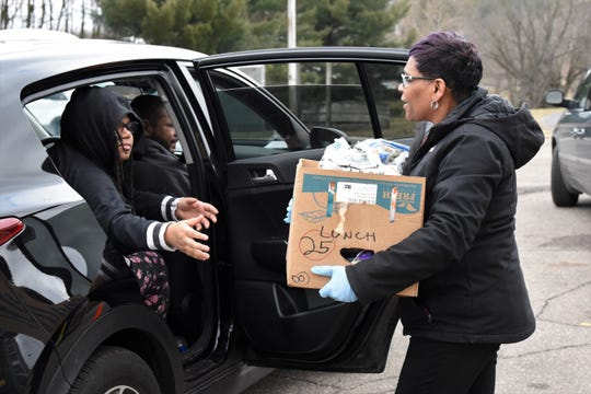 Zena Perry, site coordinator for Communities in Schools, delivers food to a student outside of Dudley Elementary. Photo by Nick Buckley for Battle Creek Enquirer.