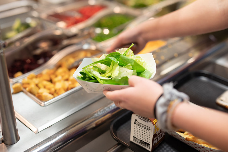 Child selects lettuce and other fresh toppings from the salad bar