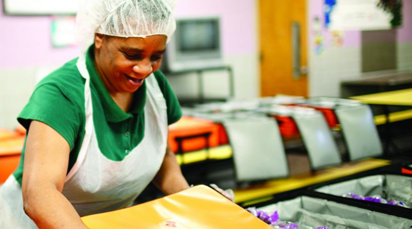 School food service worker prepares food