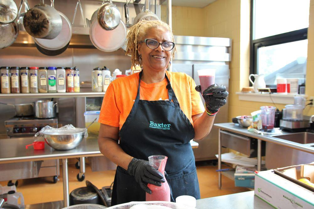 Debra Wade smiles while holding a cup of her famous purple smoothies