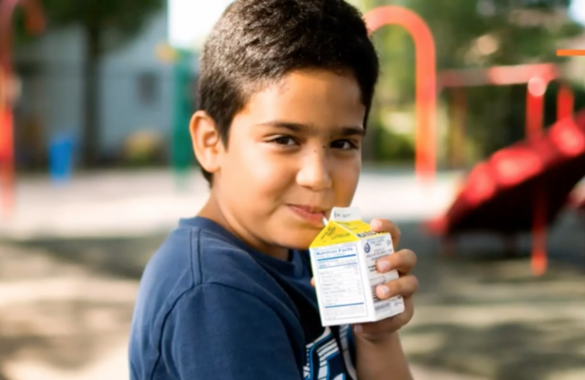 Boy drinks milk from a carton