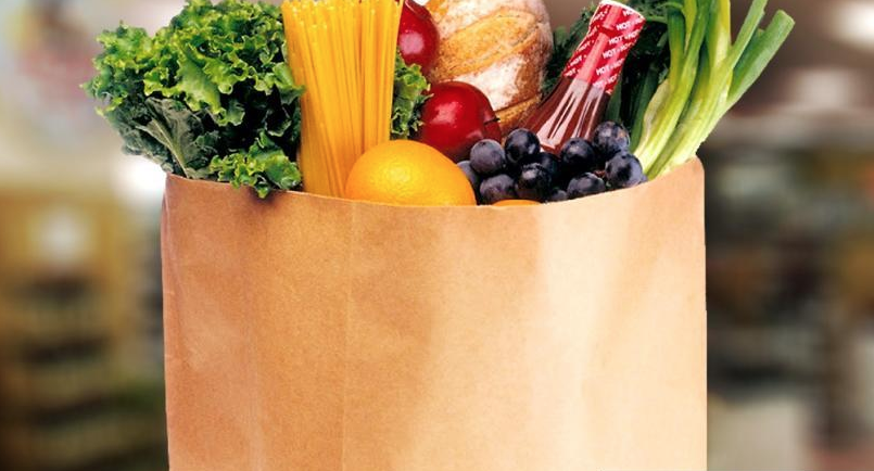 Paper grocery bag filled with fresh fruits and vegetables