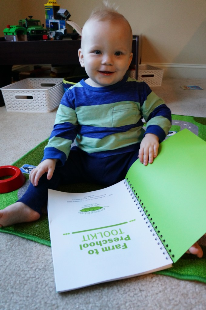 Young child with a spiral bound copy of the toolkit