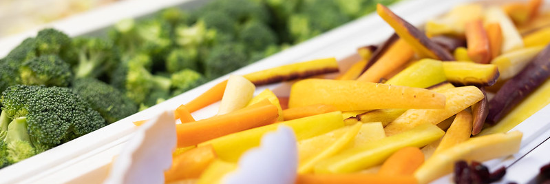 Multicolored carrot sticks and broccoli florets in an institutional food service setting