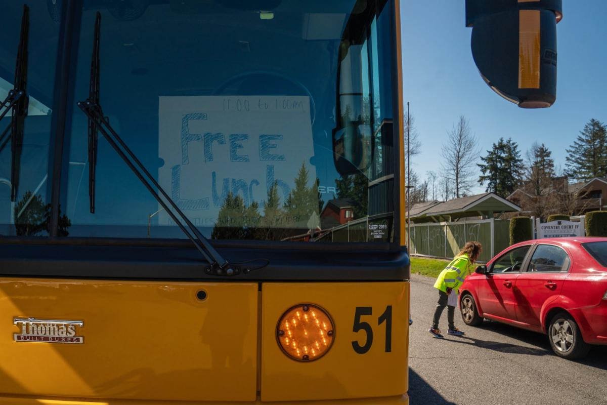 "School bus with a ""free lunch"" sign in the front window. Photo by Jovelle Tamayo for NPR."
