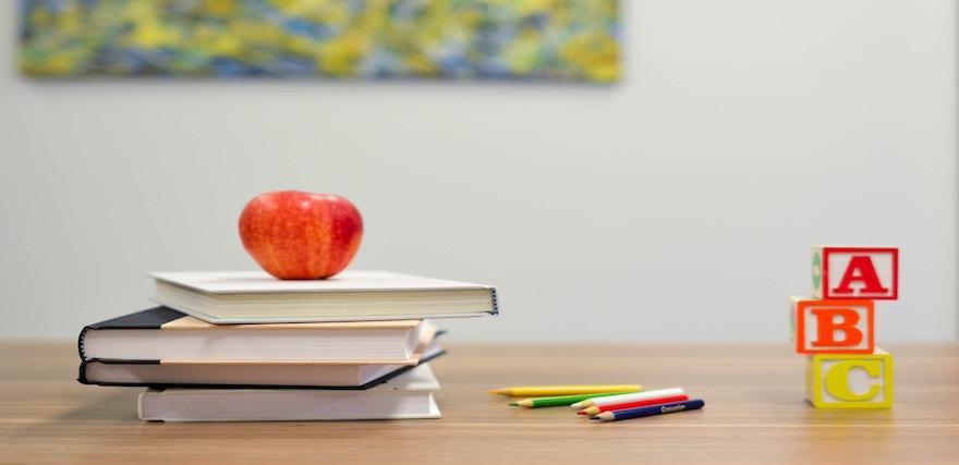 Photo of a classroom featuring an apple on a stack of books, alphabet blocks, and colored pencils