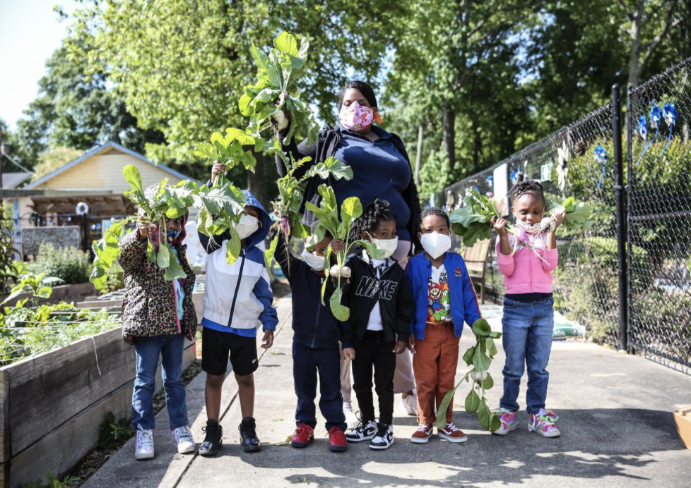 An ECE teacher stands with students in a school garden holding vegetables. Photo by Little Ones Learning Center.