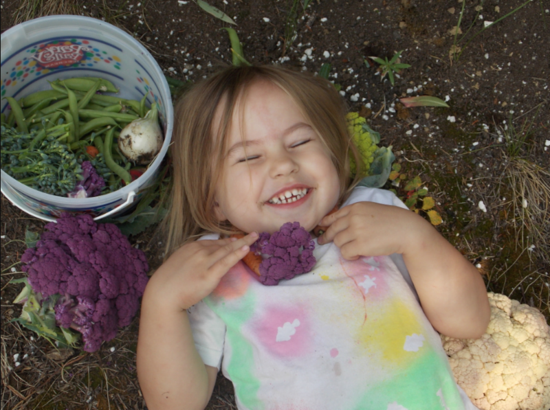 Young girl lays in a garden with purple cauliflower