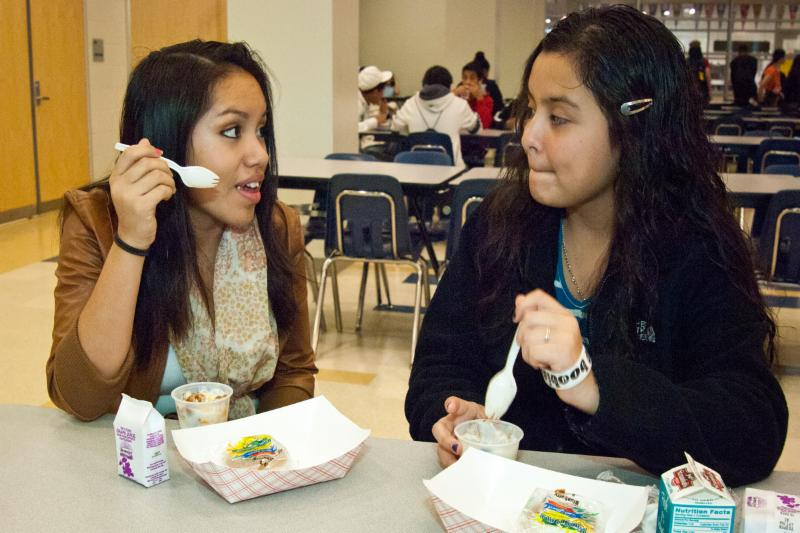 Two young women eating school lunch together in a cafeteria
