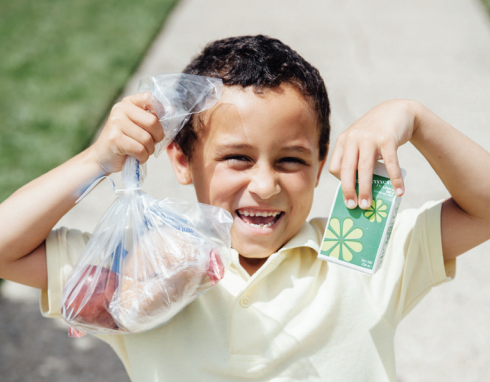 Young child smiling with school lunch