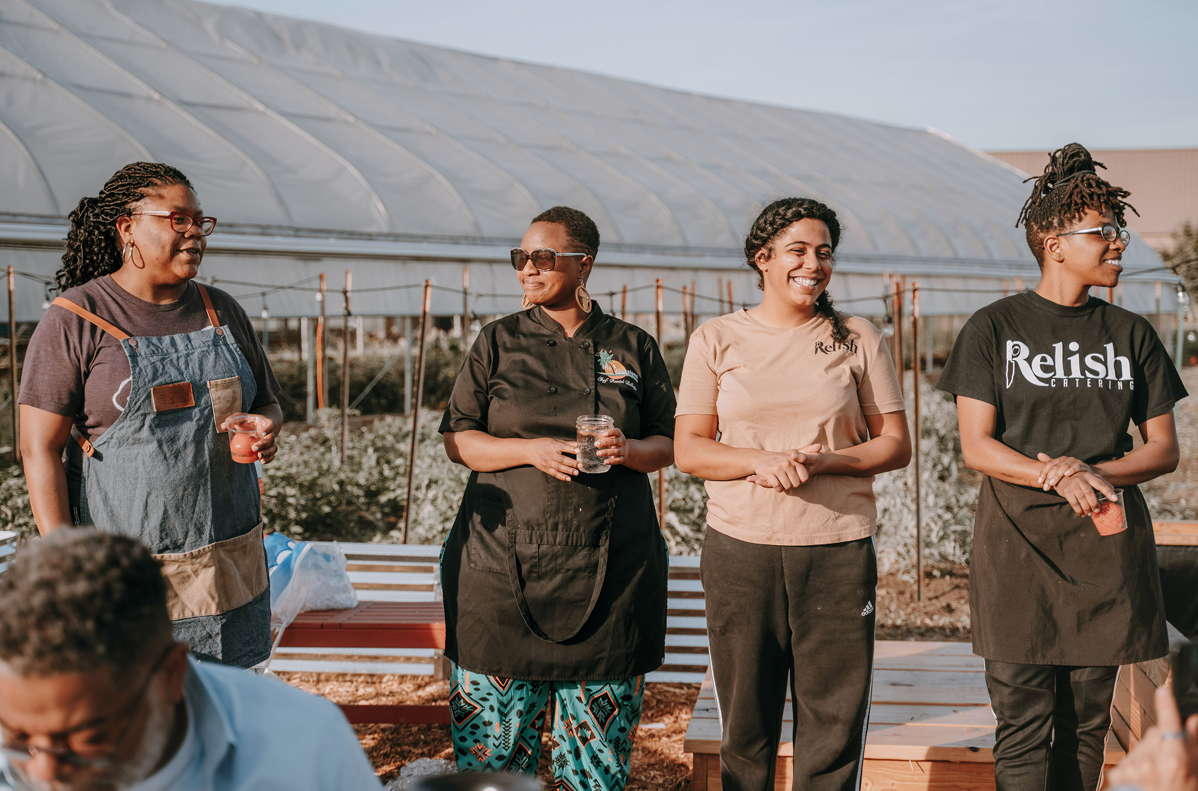 Detroit chefs and caterers stand in front of a hoophouse