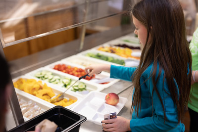 Girl serves herself at salad bar.