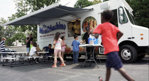 Children pick up food from a food truck