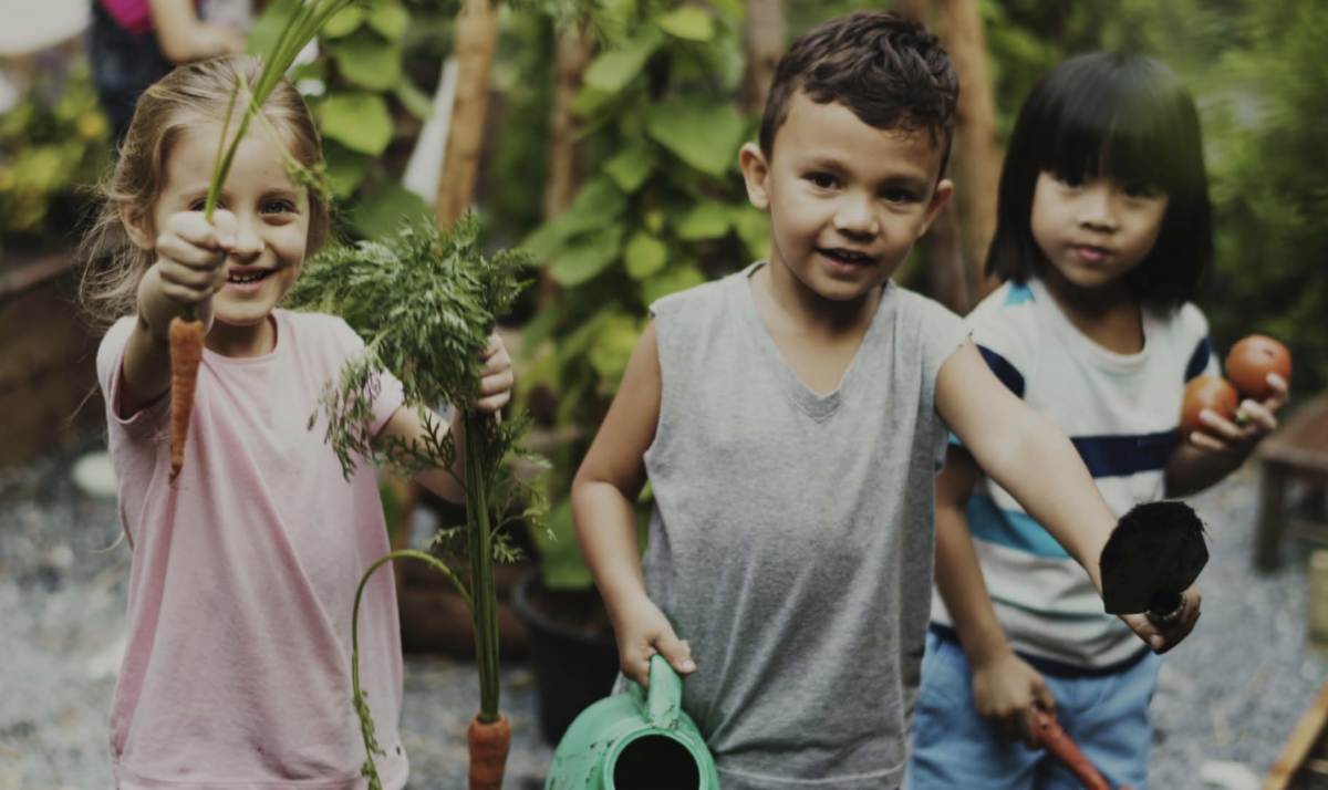 Children holding garden vegetables and a watering can
