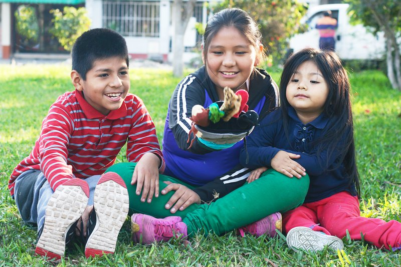 Three children play with a hand puppet in the grass