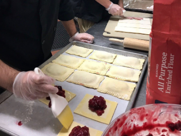 School food director brushes egg wash onto pastries.