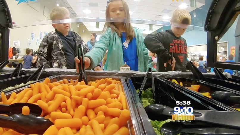 Children get fresh local vegetables at a salad bar in a Traverse City Area Public School