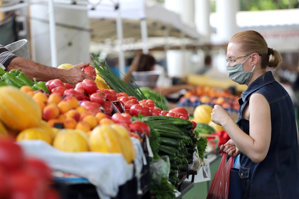 Woman wearing a mask at a farmers market in July 2020