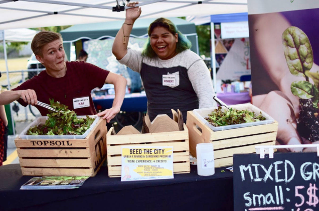 Two students working at a farm stand.