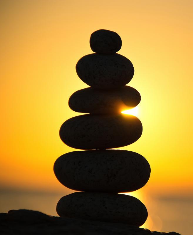 image of balanced tower of stones at sunrise