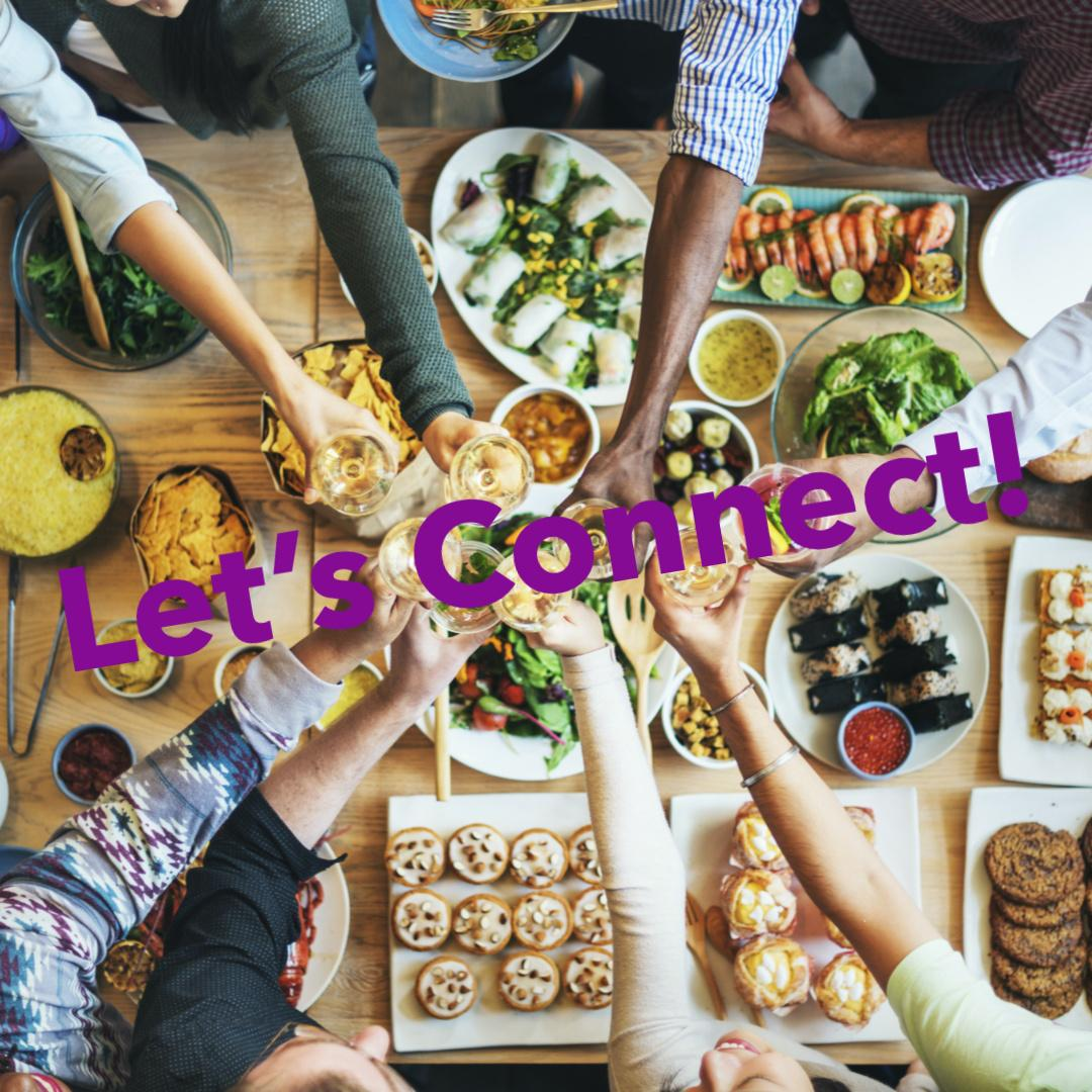 hands reaching together over a table full of foods