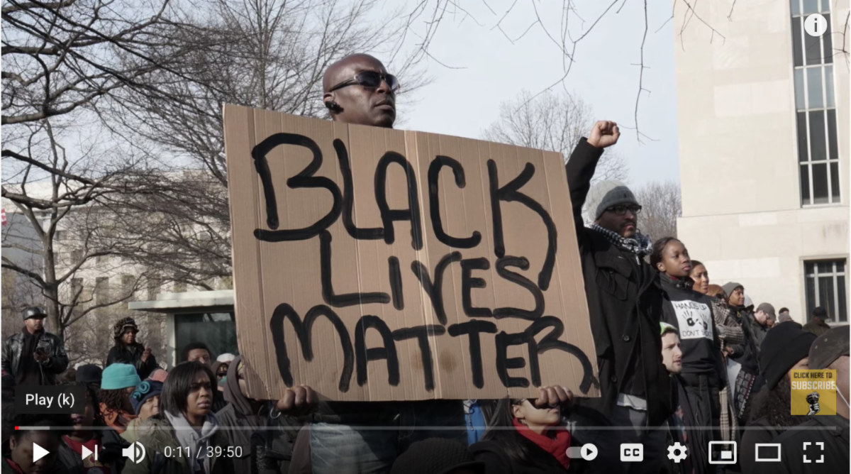 Black man holding up a #BLM sign w vimeo play buttons at bottom