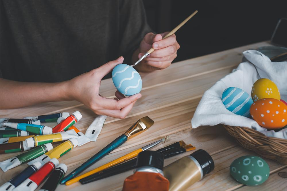 Boy with paint brush painting Easter egg