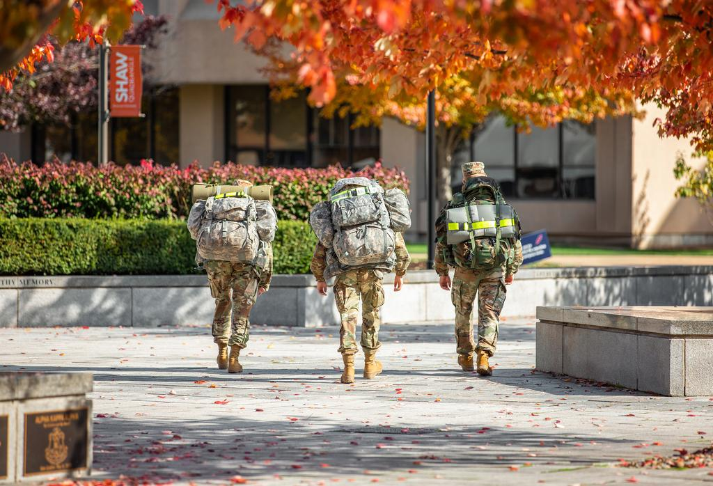 Three ROTC students carrying large packs walk through the Orange Grove on an afternoon in Autumn.