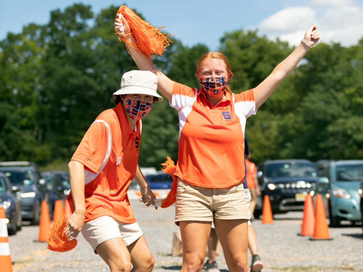 two students in orange polos wearing masks during new student move-in