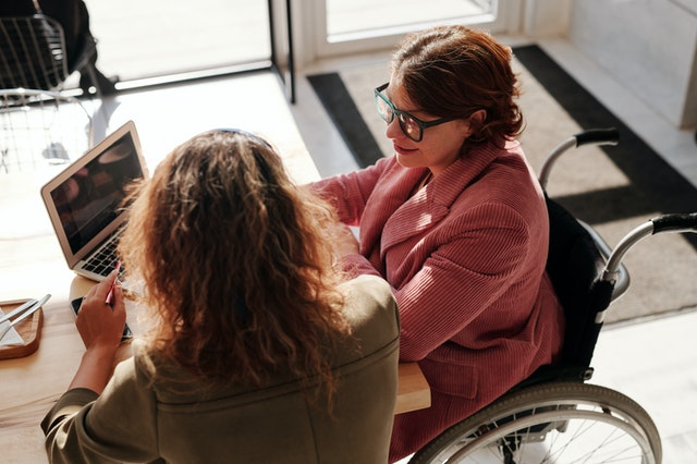 disabled woman working on laptop talking to colleague