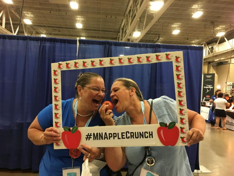 Vicki Spetlz and Lori LaBrec from Lewiston Altura crunch into an apple during the 2017 MSNA conference
