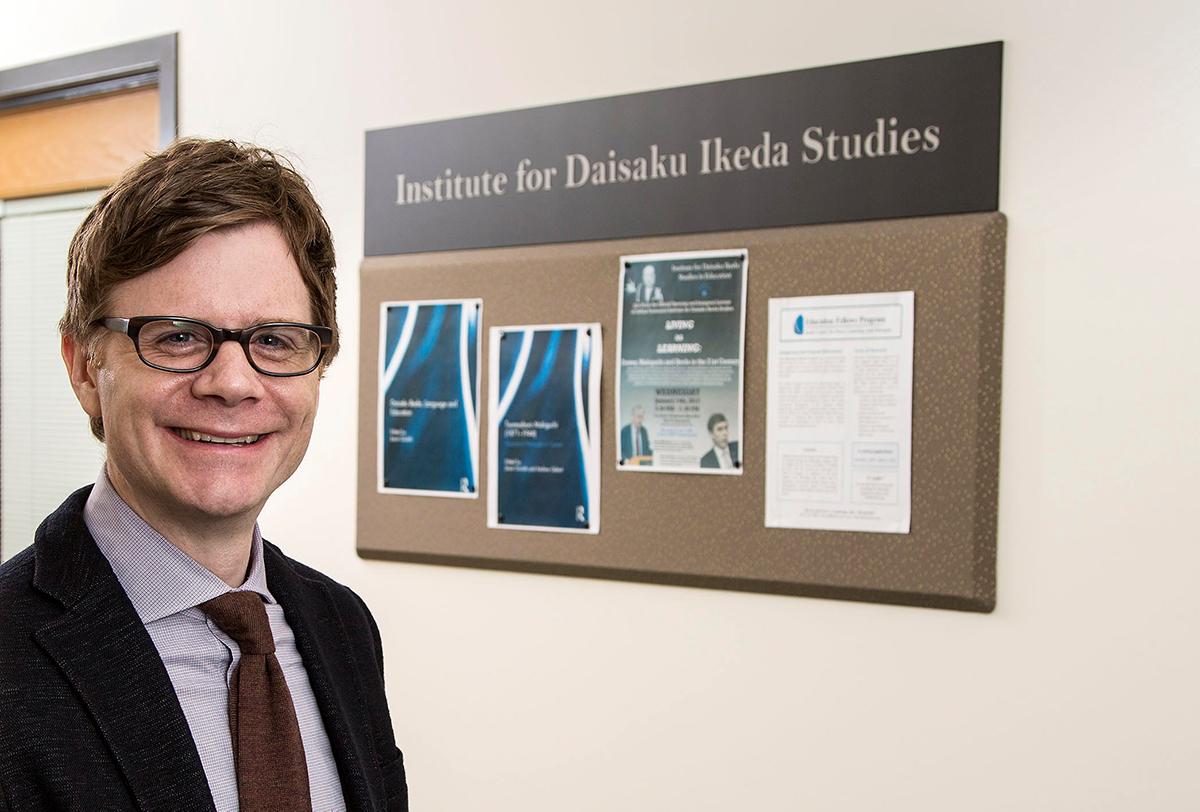 Jason Goulah stands in front of Institute for Daisaku Ikeda Studies bulletin board