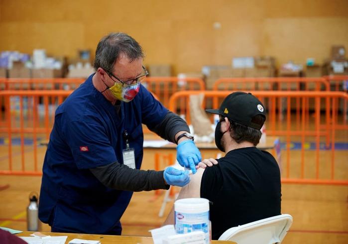 Technician vaccinates man in SUA recreation center