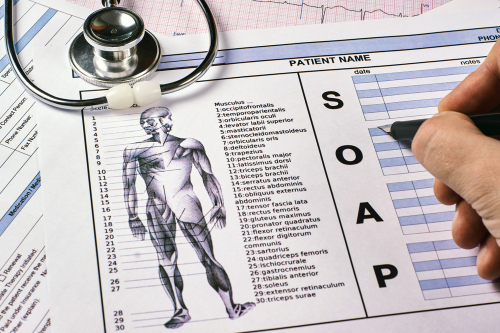Human fill a Patient SOAP note sheet_ stethoscope on corkwood background. Flat lay.