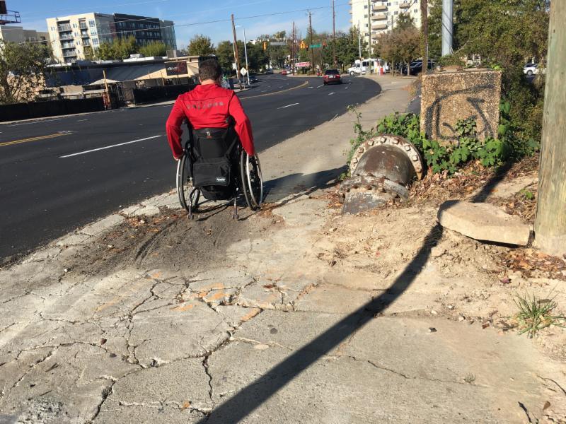 Wheelchair user navigating broken sidewalks on Peachtree Rd