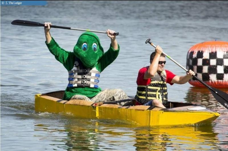 Picture of Public Works Mascot and an employee in the cardboard boat race.