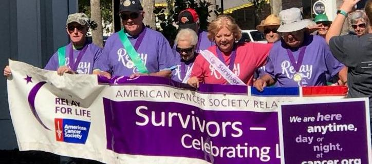 Picture of Relay for Life survivors walking around with a Survivors - Celebrating Life banner.