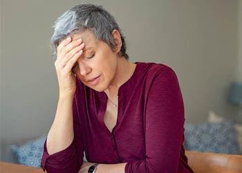 Woman with hand on head feeling dizzy.