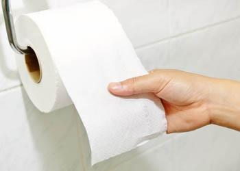 Woman's hand pulling toilet paper roll