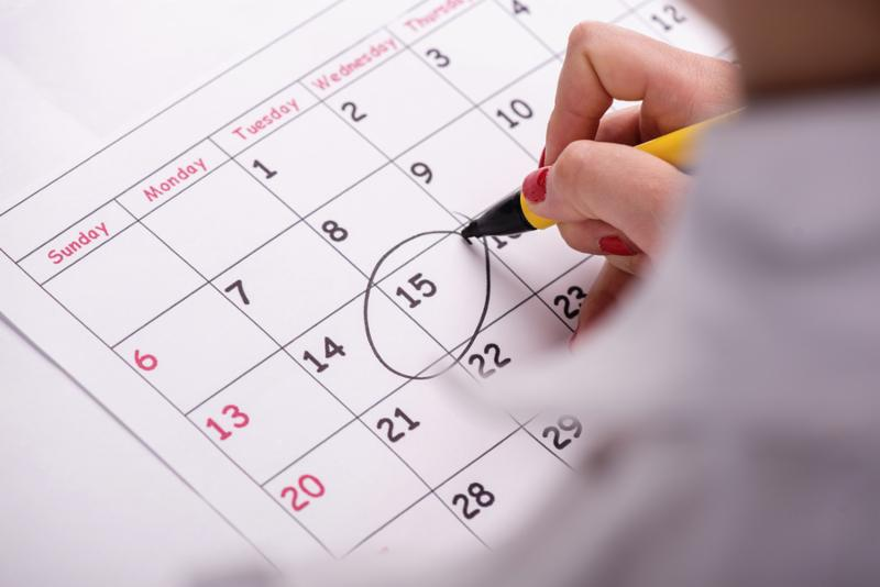 Close-up top-view photo of calendar with a datum circled by young woman with red nails with a back marker, concept of time management at work