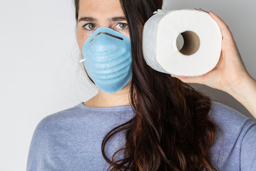 A woman is wearing a face mask for protection from the Corona Virus and has stocked up on her toilet paper stash in case of quarantine.