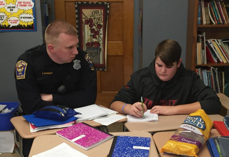 Police officer and student at desks