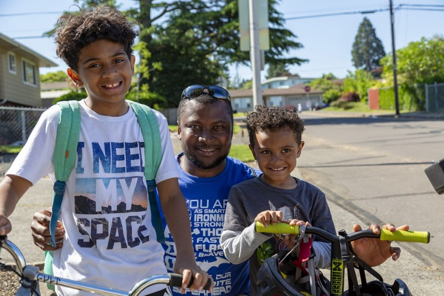 Man with two school-aged children riding their bikes to school.