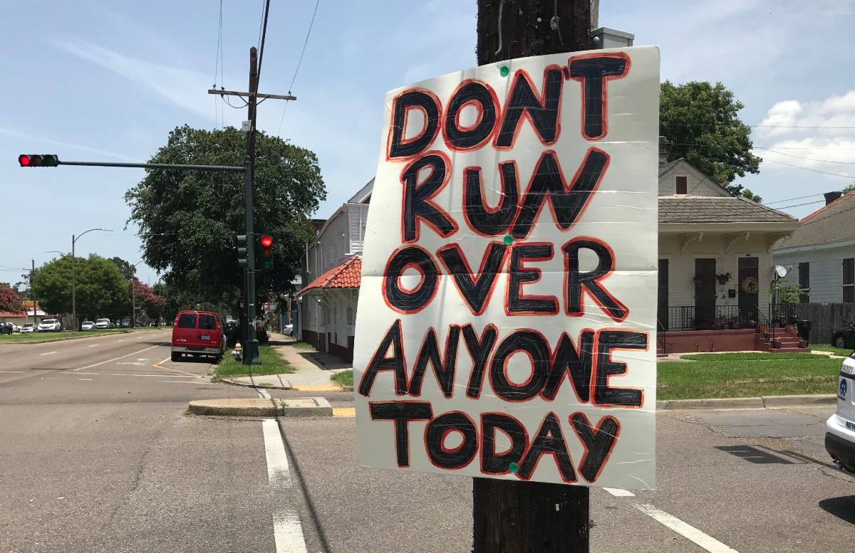 """A street activism sign by a citizen near a crosswalk that reads, """"Don't run over anyone today"""""""