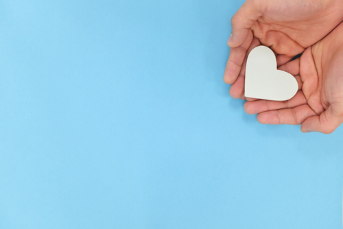 Hands holding a white heart in blue background with copy space. Kindness_ charity_ pure love and compassion concept.