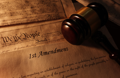 First Amendment and US Constitution text with legal gavel